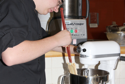 A student mixes ingredients in a bowl